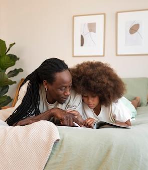 Vista frontal de pai e filha lendo um livro juntos