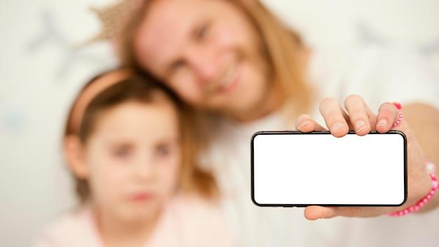 Vista frontal de pai e filha segurando um smartphone com espaço de cópia