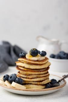 Vista frontal de panquecas de café da manhã com amoras e fatias de banana