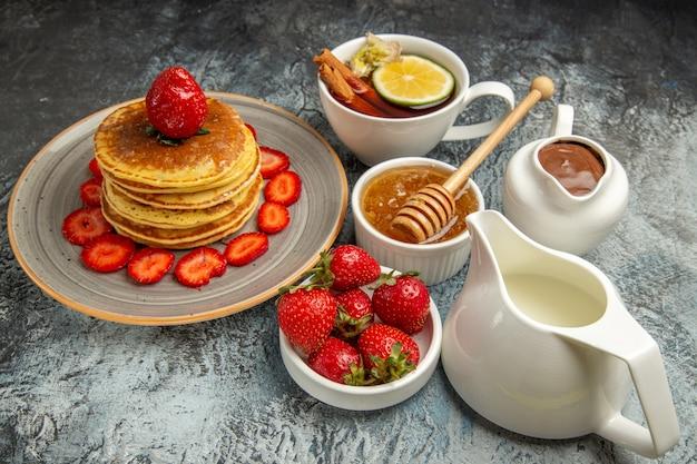 Vista frontal de panquecas deliciosas com frutas e uma xícara de chá na superfície clara de bolo doce de frutas