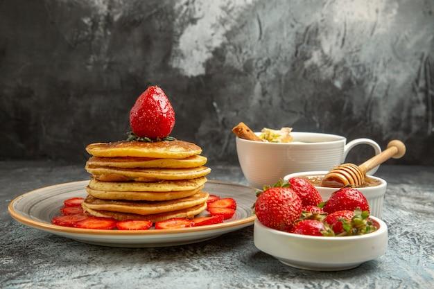 Vista frontal de panquecas deliciosas com morangos e uma xícara de chá em um bolo de frutas de superfície leve