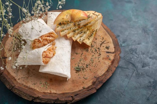 Vista frontal de pão sírio enrolado fatiado com recheio de carne na mesa azul escura