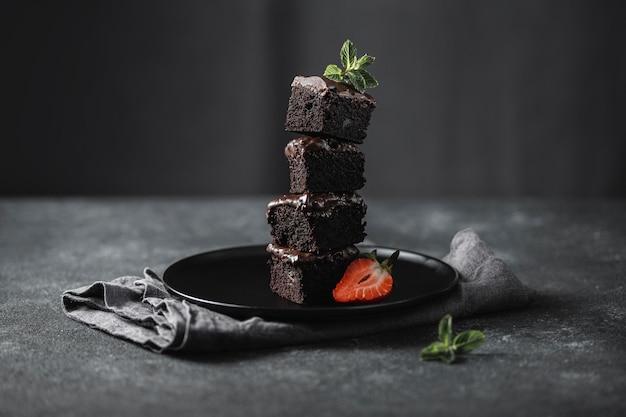 Vista frontal de pedaços de bolo de chocolate no prato com hortelã