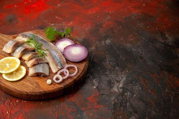 Vista frontal de peixe fresco fatiado com anéis de cebola e limão na refeição escura carne, frutos do mar, foto colorida, lanche grátis.