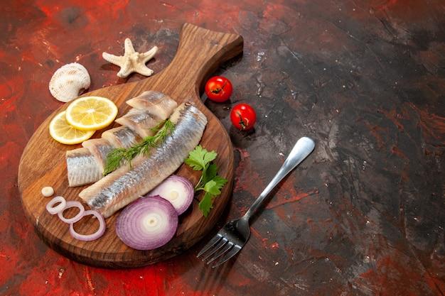 Vista frontal de peixe fresco fatiado com anéis de cebola em salada de frutos do mar de cor escura salgadinho de carne
