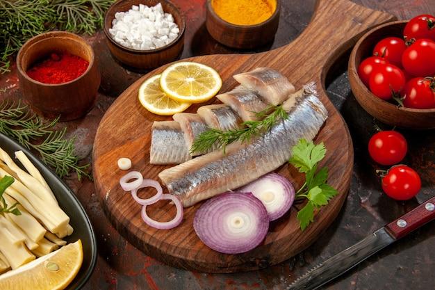 Vista frontal de peixe fresco fatiado com temperos e anéis de cebola em frutos do mar de cor escura salada madura