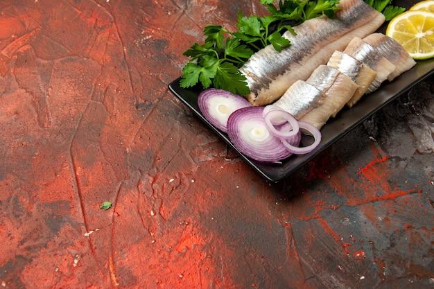 Vista frontal de peixe fresco fatiado com verduras e cebola dentro de uma panela preta na foto de refeição de cor escura de frutos do mar