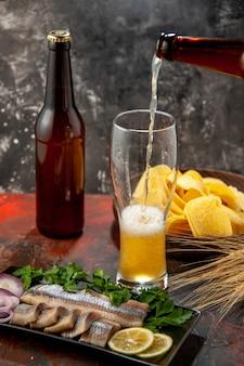 Vista frontal de peixe fresco fatiado com verduras e cerveja no escuro