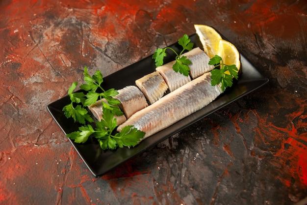 Vista frontal de peixe fresco fatiado com verduras e pedaços de limão dentro de uma panela preta sobre comida de carne escura