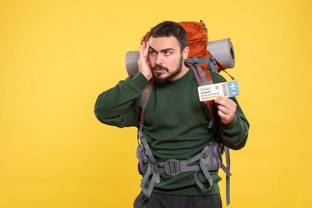 Vista frontal de pensar cara viajando com mochila e segurando o bilhete em fundo amarelo