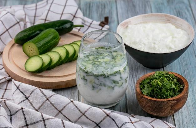 Vista frontal de pepinos fatiados em um carrinho de iogurte com verduras e okroshka em um copo em uma superfície cinza