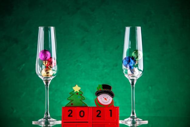 Vista frontal de pequenas bolas de natal em taças de vinho em blocos de madeira na superfície verde