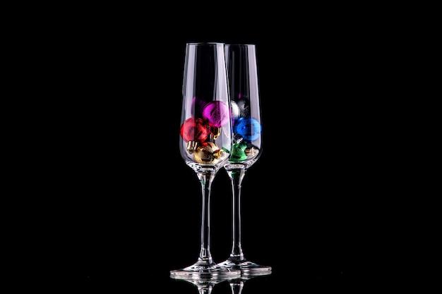 Vista frontal de pequenas bolas de natal em taças de vinho na superfície escura