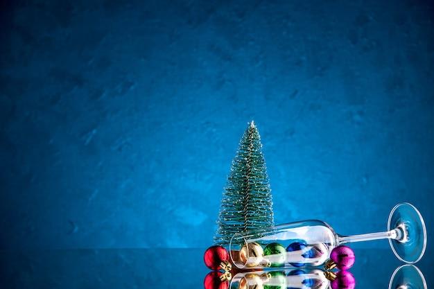 Vista frontal de pequenas bolas de natal espalhadas em uma pequena árvore de natal em vidro de vinho na superfície azul escuro