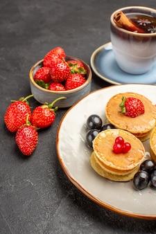 Vista frontal de pequenas panquecas saborosas com frutas e xícara de chá em frutas de bolo de torta de superfície cinza