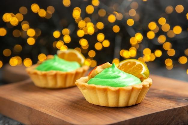 Vista frontal de pequenas tortas em uma tábua em uma superfície escura com luzes de natal