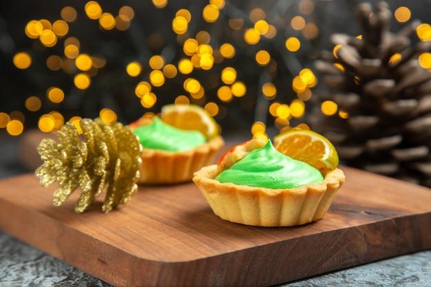 Vista frontal de pequenas tortas na tábua de cortar enfeites de natal em uma superfície escura com luzes de natal