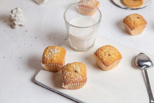 Vista frontal de pequenos bolos deliciosos com açúcar em pó e copo de leite na superfície branca