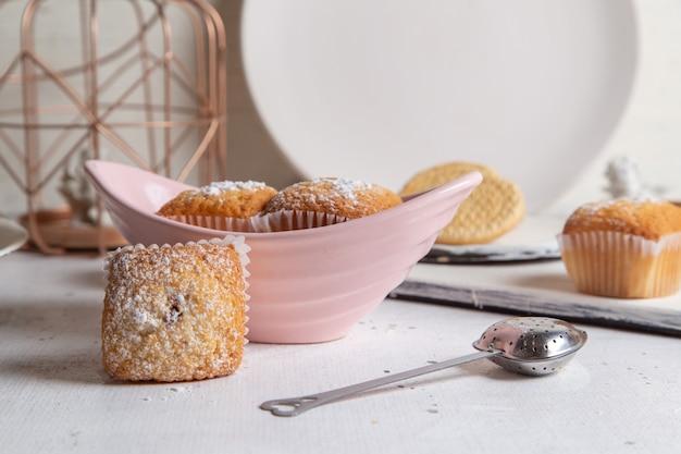 Vista frontal de pequenos bolos deliciosos com açúcar em pó na superfície branca