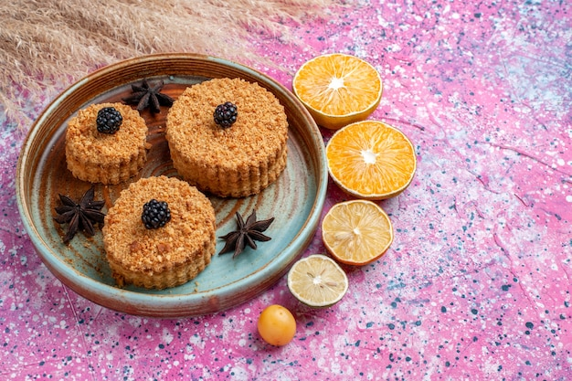 Vista frontal de pequenos bolos deliciosos com rodelas de laranja na superfície rosa