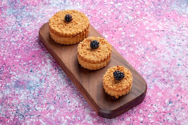 Vista frontal de pequenos bolos deliciosos redondos formados na superfície rosa