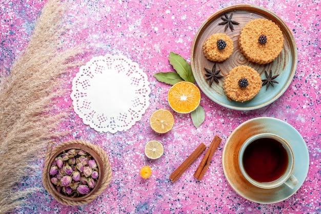 Vista frontal de pequenos bolos gostosos, doce e delicioso prato interno com chá na superfície rosa