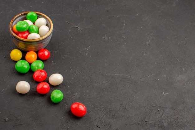 Vista frontal de pequenos doces coloridos no espaço escuro