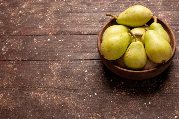 Vista frontal de peras frescas maduras, verdes e suculentas no espaço marrom