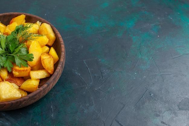 Vista frontal de perto, batata cozida fatiada refeição deliciosa com verduras dentro de um prato marrom na superfície azul escura