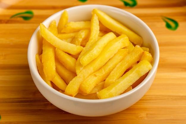 Vista frontal de perto batatas fritas cozidas dentro de um prato branco na mesa de madeira.