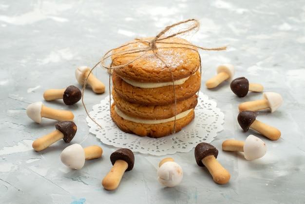 Vista frontal de perto biscoitos cremosos com diferentes capas de chocolate, forrados com biscoitos recheados na superfície de luz cinza.
