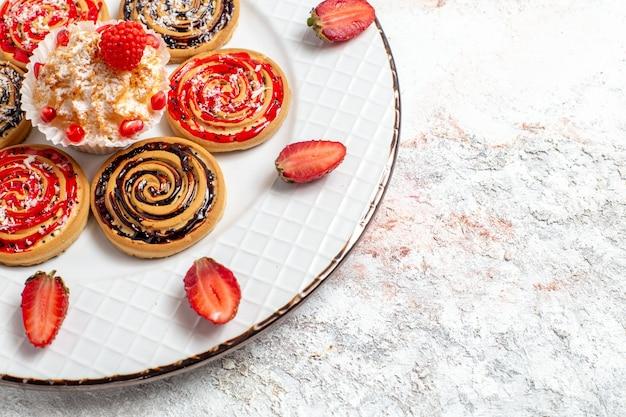 Vista frontal de perto biscoitos doces redondos formados dentro da placa no espaço em branco