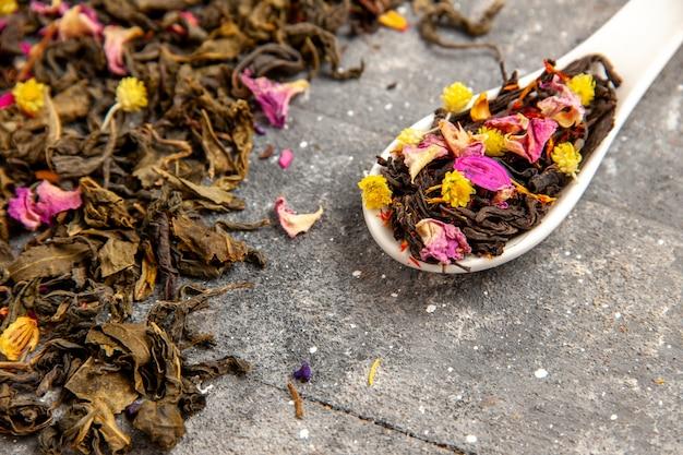 Vista frontal de perto chá frutado seco fresco com sabor de flor no espaço rústico cinza