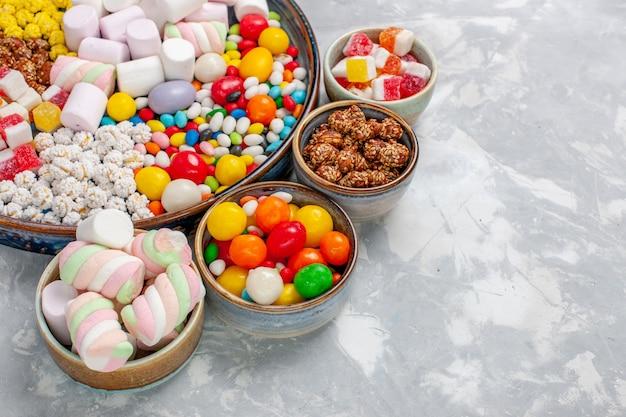 Vista frontal de perto, composição de doces de diferentes cores e marshmallow na mesa branca