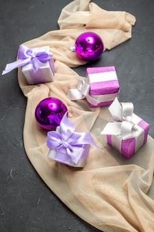 Vista frontal de perto de acessórios de decoração de presentes coloridos para o ano novo em toalha de cor nude em fundo preto