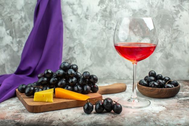 Vista frontal de perto de delicioso cacho de uva preta e queijo fresco em uma tábua de madeira e em uma panela marrom, um copo de vinho no fundo de cor mista