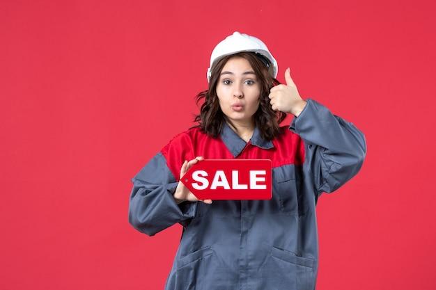 Vista frontal de perto de uma trabalhadora curiosa de uniforme usando capacete mostrando o ícone de venda e fazendo um gesto de ok na parede vermelha isolada