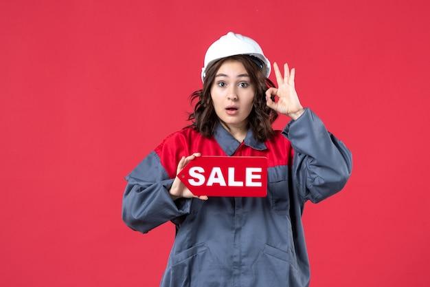 Vista frontal de perto de uma trabalhadora surpresa de uniforme usando capacete, mostrando o ícone de venda e fazendo gesto de óculos na parede vermelha isolada