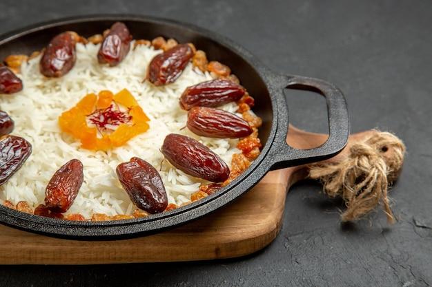 Vista frontal de perto deliciosa refeição de arroz plov cozido com khurma e passas na superfície escura prato de arroz plov cozinhando