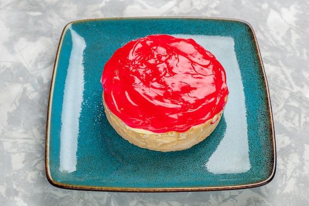 Vista frontal de perto deliciosa torta de bolo com creme vermelho na superfície branca