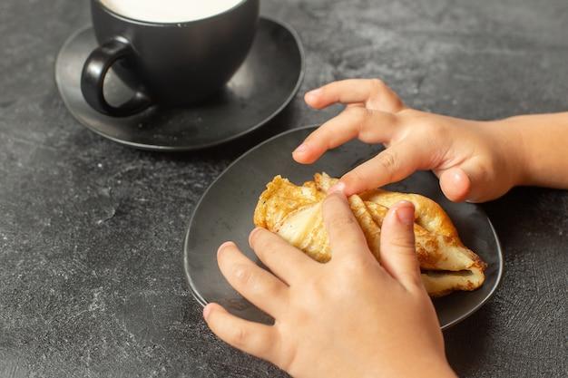 Vista frontal de perto deliciosas panquecas com leite na mesa escura