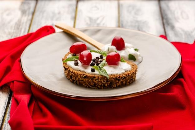 Vista frontal de perto deliciosas torradas de pão com creme de leite e dogwoods dentro de placa de luz em cinza