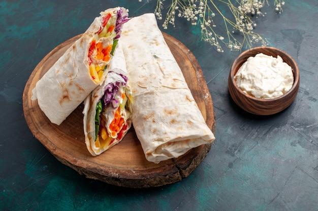 Vista frontal de perto delicioso sanduíche de carne feito de carne grelhada no espeto com creme de leite na mesa azul