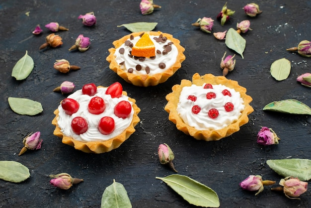Vista frontal de perto deliciosos bolos com creme com frutas no topo isolados na superfície escura açúcar doce fruta