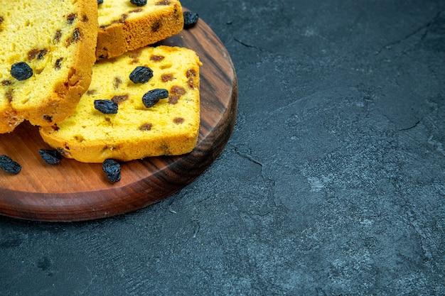 Vista frontal de perto deliciosos bolos de passas cortados em um espaço azul escuro