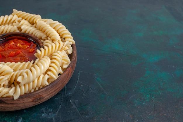 Vista frontal de perto em forma de massa italiana com molho de tomate em superfície azul escura