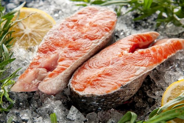 Vista frontal de perto fatias de peixe fresco com limão e gelo na foto cor escura prato carne comida escuridão frutos do mar