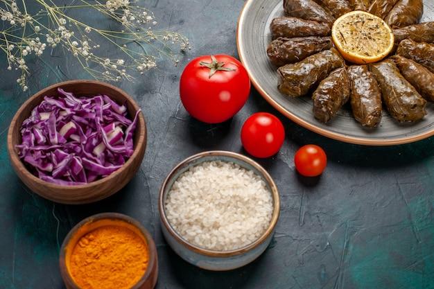 Vista frontal de perto folha dolma deliciosa refeição de carne oriental enrolada dentro de folhas verdes com tomates e temperos na mesa azul