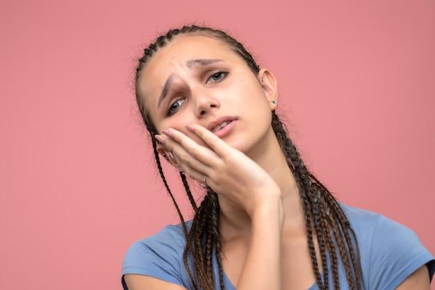 Vista frontal de perto jovem cansada em rosa