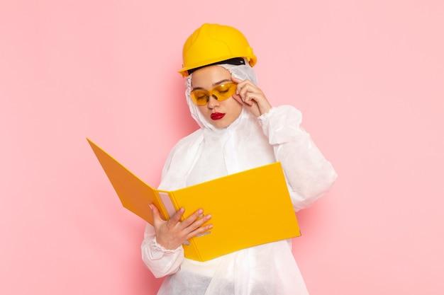 Vista frontal de perto jovem linda mulher em um terno branco especial usando capacete protetor, lendo um arquivo rosa